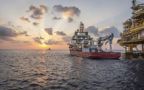 production platform rig and supply boat in oil field